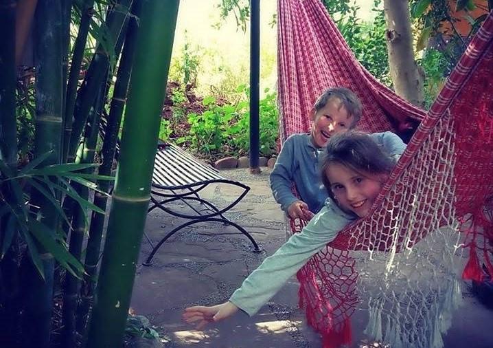 Dvě děti dovádí v houpací síti.