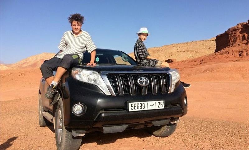 Dva chlapci sedí na kapotě terénního vozidla uprostřed pouště.
