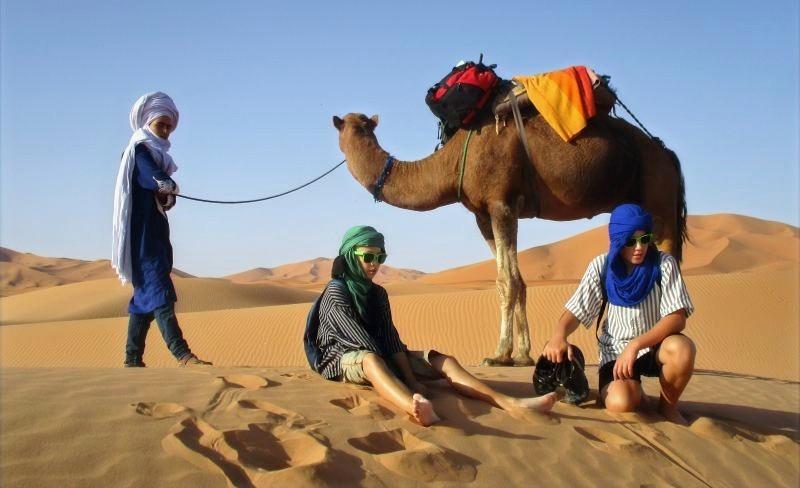 Dva malí chlapci v turbanech odpočívají na poušti.