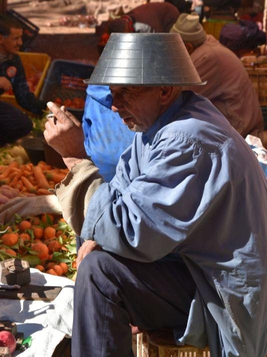 Sedící muž s kýblem na hlavě