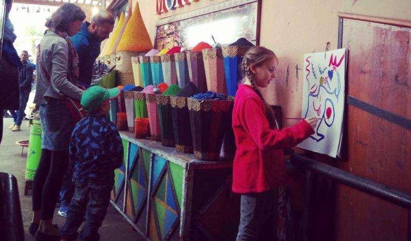 Dívka kreslí obrázek u výběru marockých barev.