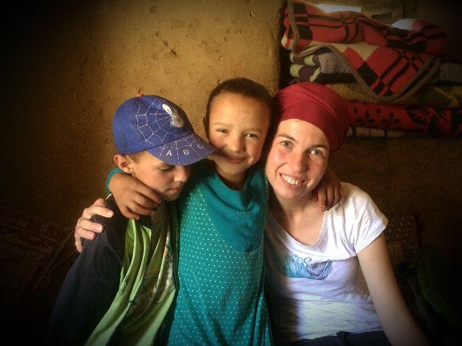 Chlapec v modre ksiltovce, uprostred divka v modrem a vpravo Tereza Huclova v cervenem turbanu, vsichni se objimaji