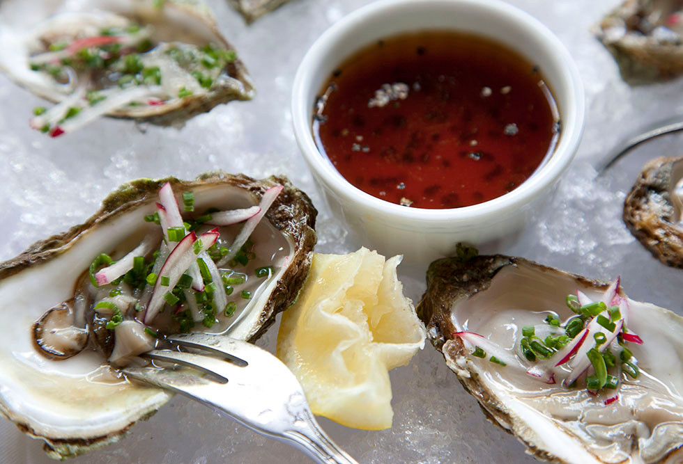 Photo of Oysters on the Half-Shell with slice of lemon and black pepper ponzu sauce.