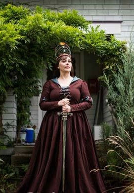 Naarah McDonald as a queen with sword and crown.