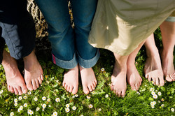 Healthy feet series_ feet of men and women of different ages in the grass with daisies, seen from ab