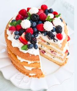 Layered Victoria sponge cake with fresh whipped cream and piled high with fruit
