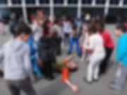 un clown allongé au sol, des enfants le regardent