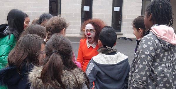 Une clowne face a des enfants