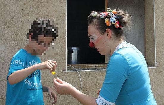 Un enfant donne une fleur a une clown