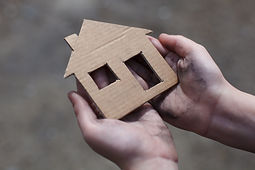 homeless boy holding a cardboard house,