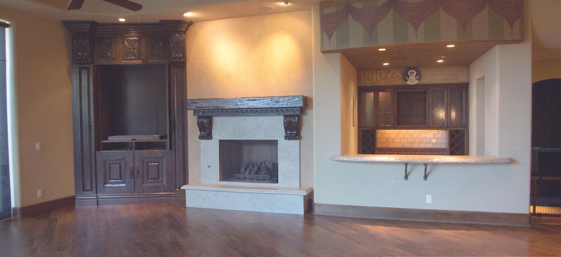 The orginal great room housed a heavy wooden TV case that no longer worked with today's flat screens, a fire place and a dated bar area.  We removed the built in and created an entire new focal wall for the fireplace and TV. The bar also got a refreshing contemporary new look.