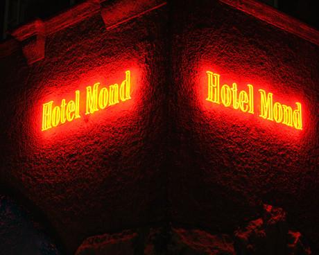 """Alt-Berliner Fassade, die von der rot leuchtenden Neonschrift """"Hotel Mond"""", ein altes Hotel in Berlin, erhellt wird"""