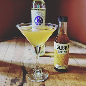 Mead cocktail in a martini glass, next to a bottle of Bubbs Bitters and Elgin Mead