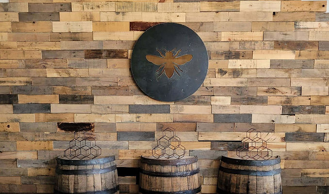 three barrels with wine holders on top against a wood wall with honey bee metal sign. Elgin Meadery.