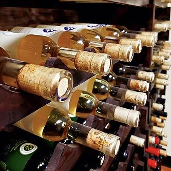 Bottles of golden mead, on wine rack.