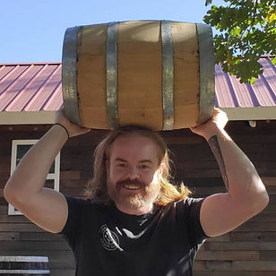 Elign Meadery founder, Micah Erwin lifts a wooden aging barrel, and smiles.