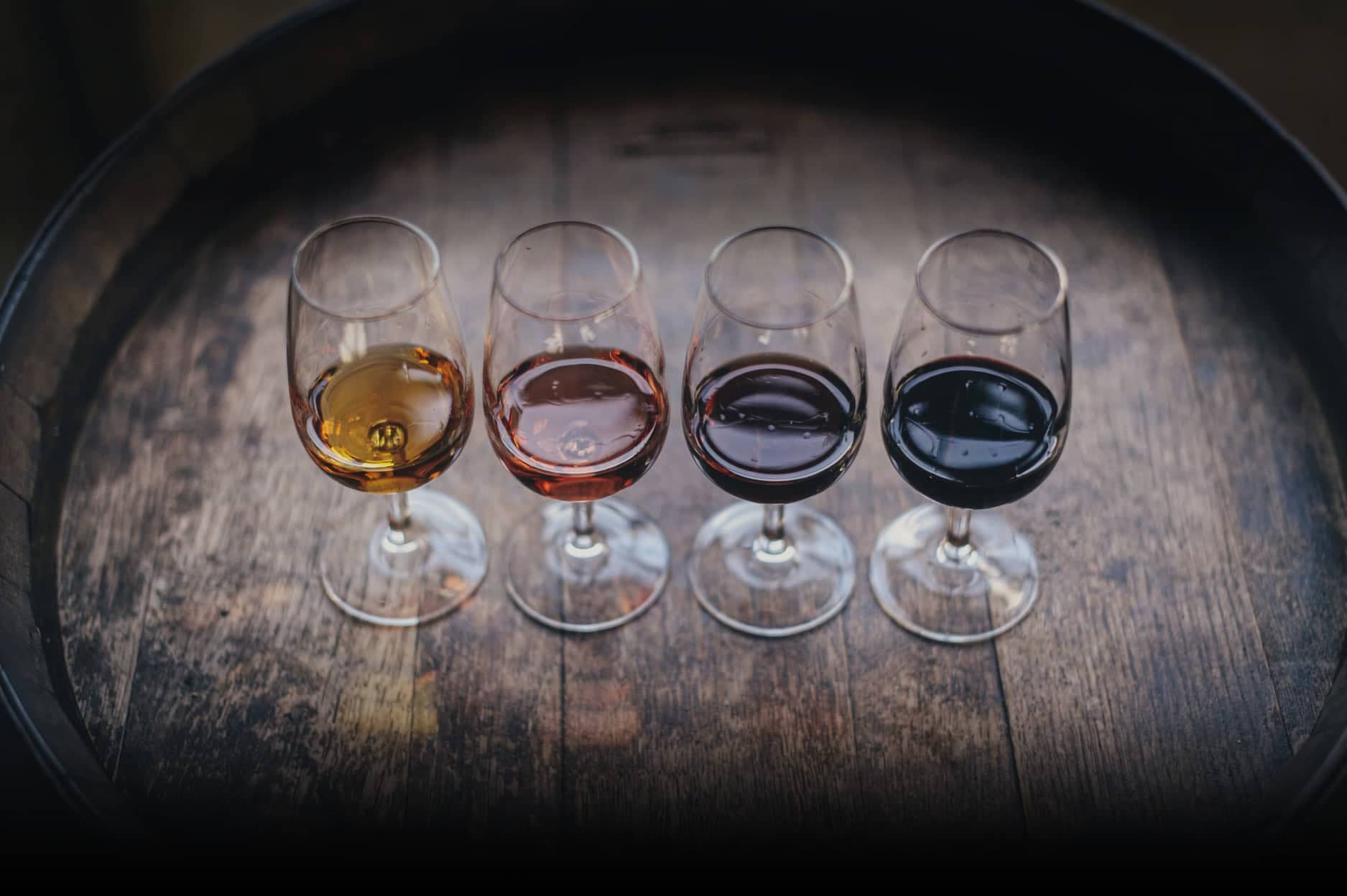 four glasses of mead ranging from golden to dark red sit on a rustic wooden aging barrel. buy mead.