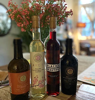 Four bottles of different Eglin Meads, sitting on a table with flowers. Cherry Blossom mead, Peach-apricot mead, black currant cutra hops mead, and black mead.