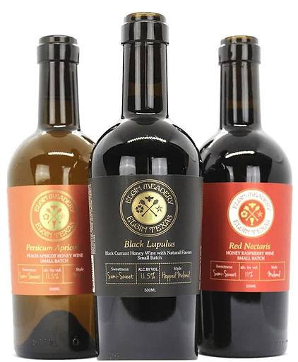 Three bottles of Elgin Mead. In front, Black Lupulus. Left: Persicum Apricotus, Right: Red Nectaris.