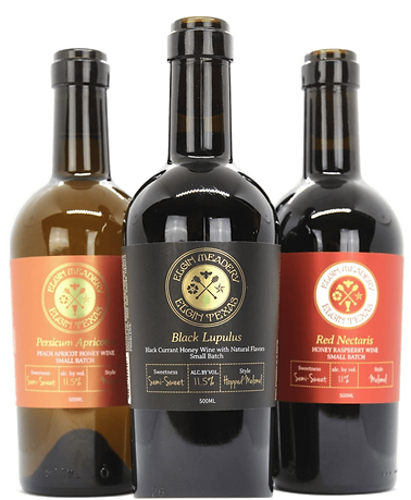 Three bottles of Elgin mead on a white background. The bottles are made of dark glass, and the lables on the bottles reads,'Persicum Apricotus, Black Lulupus, and Red Nectaris.