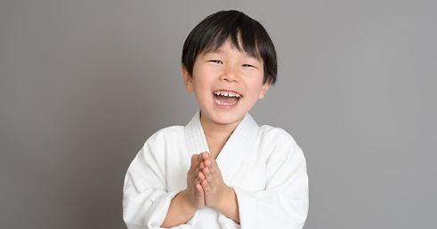 Smiling young athlete boy wearing judugi