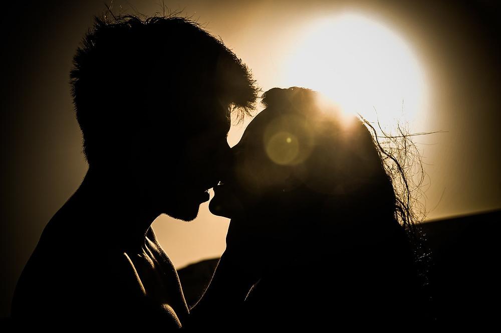 Pareja besándose en un atardecer