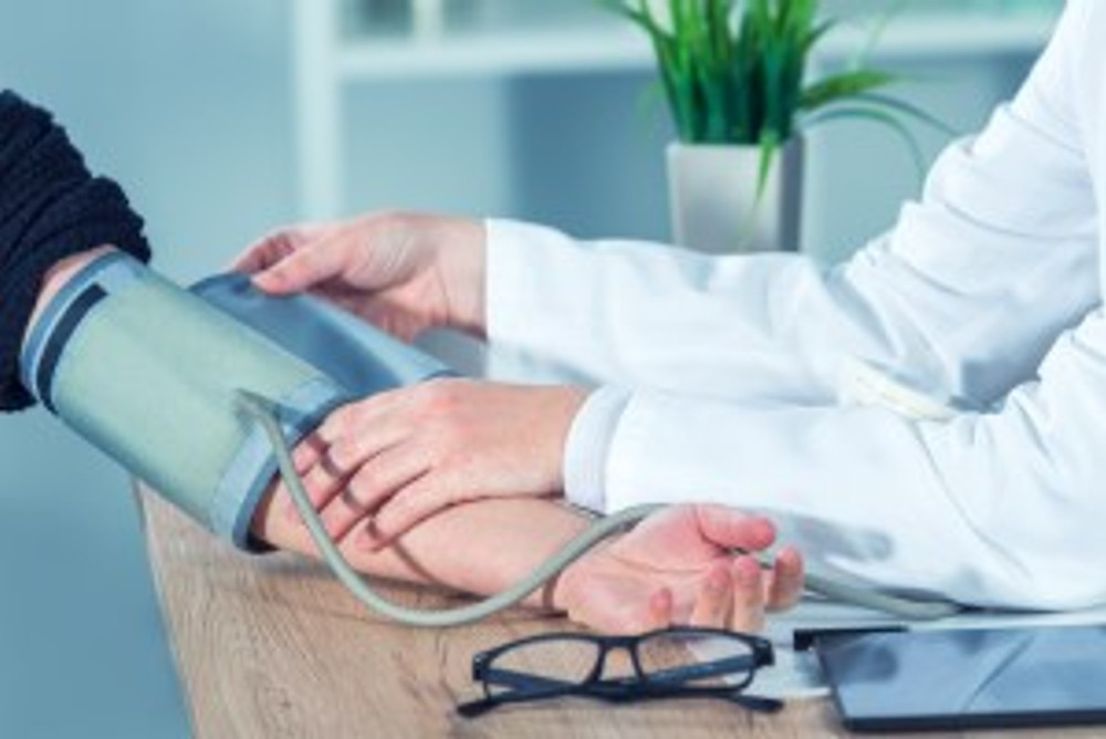 Doctor measuring blood pressure - cardiac health is important for brain health