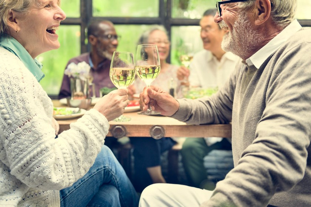 Mature adult friends drinking wine which should be no more than 5 oz/day for women