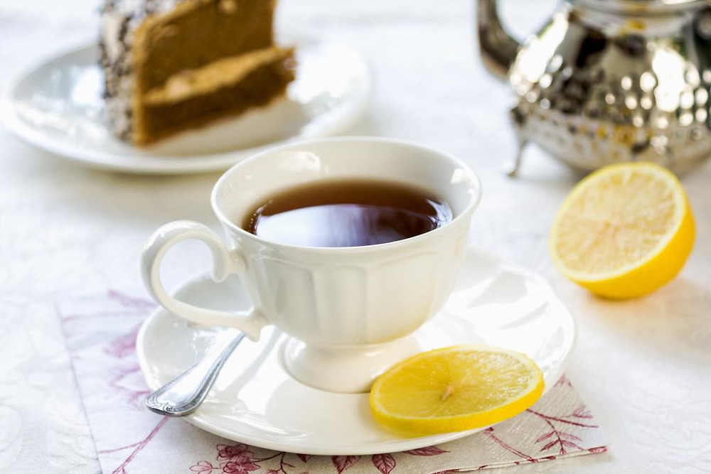 Tea cup with lemon and cake in background