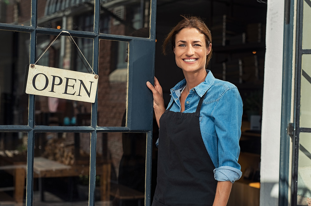 Happy mature woman owner showing open sign in her small business shop.