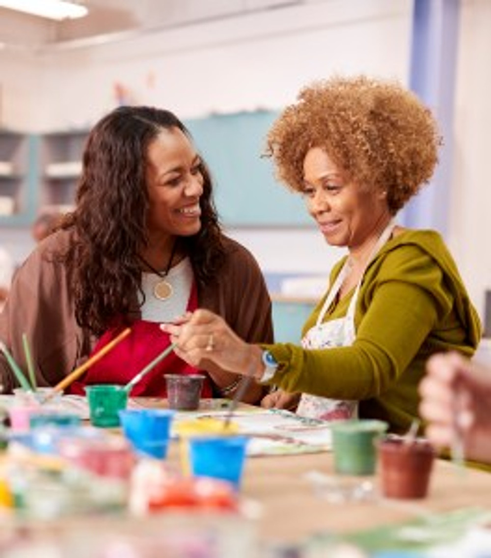 Two Mature Women Attending Art Class In Community Centre Together