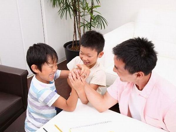 子どもたちと腕相撲で遊ぶパパ