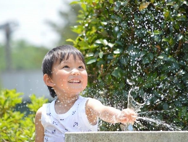 公園の水飲み場で遊ぶ子ども