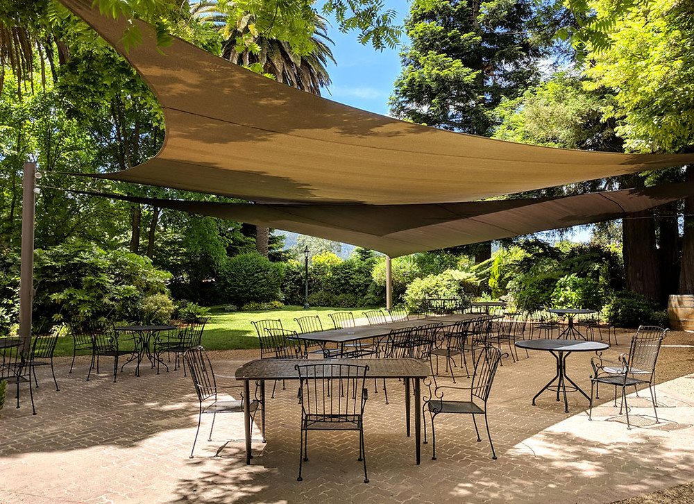Overlapping shade sails over an outdoor patio and dining area.