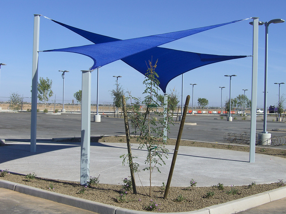Two, blue shade sails over a patio.