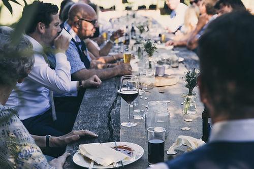 Un verre de vin rouge posé sur une table où il ya un repas, un homme derrière boit une bière. Des petits bouquets de fleurs sont en décoration sur la table