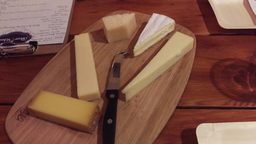 A picture of five diferent cheeses on a cheese board before the class started.