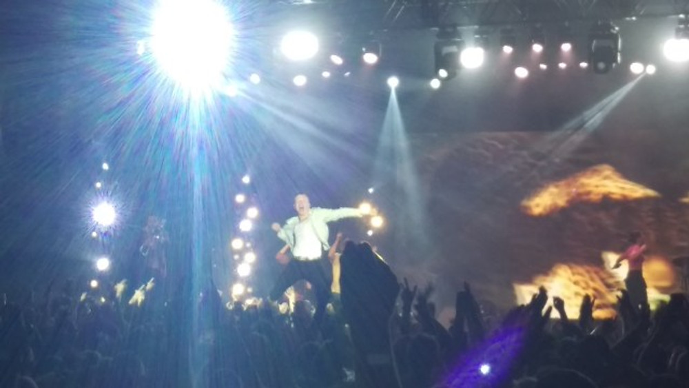Macklemore standing on the hands of the crowd and performing.