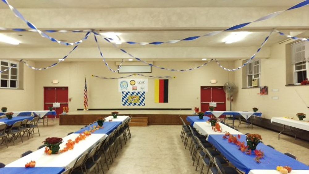 Picture of some long tables and chairs in a church hall decorated for Oktoberfest.