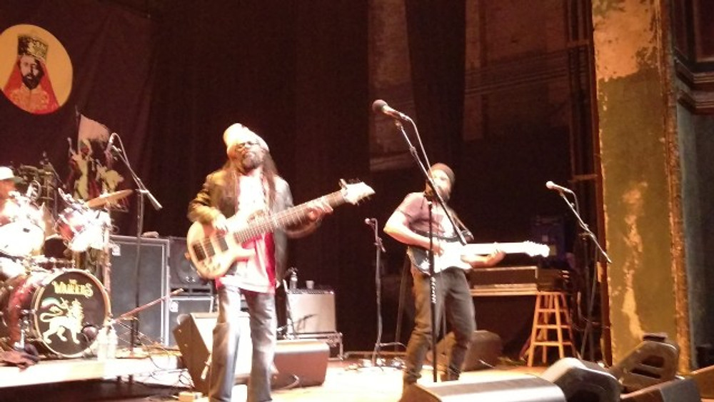 Two of The Wailers on stage playing rhythm guitar and bass.