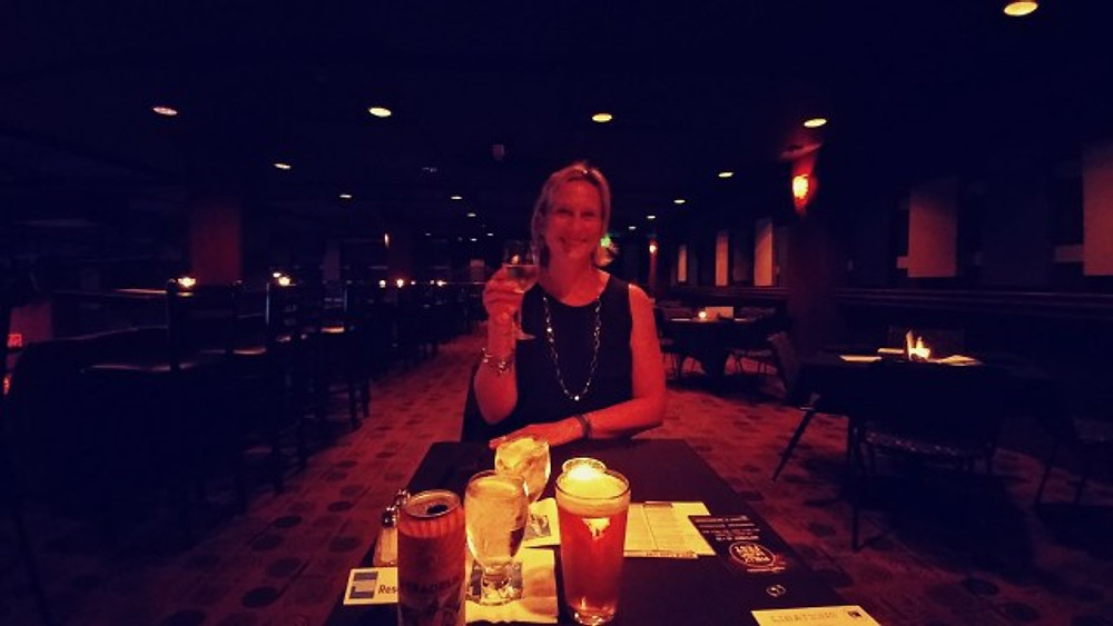 Holding up a glass of wine and getting ready to have dinner at World Cafe Live.