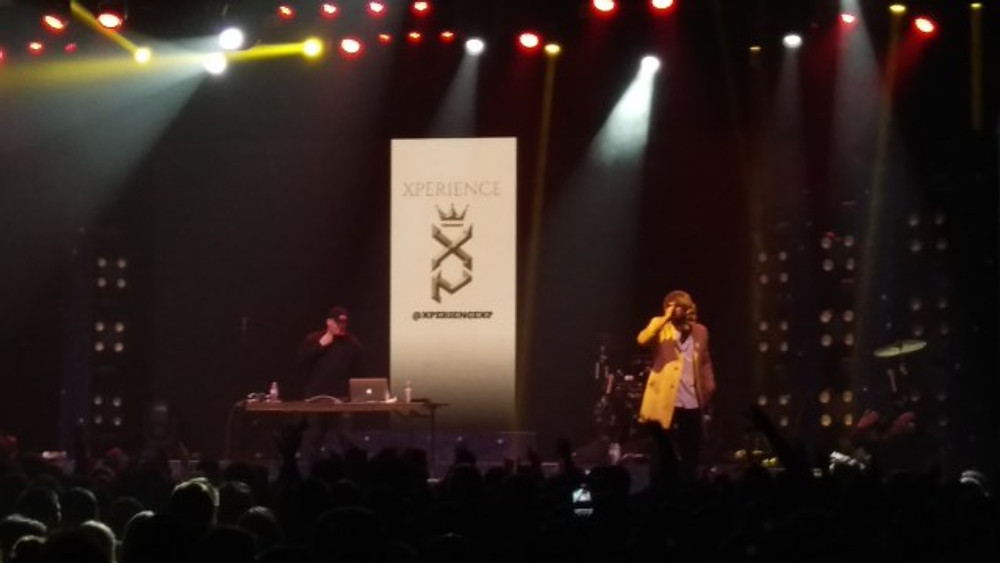 A picture of rapper Xperience on stage, with his DJ behind him.