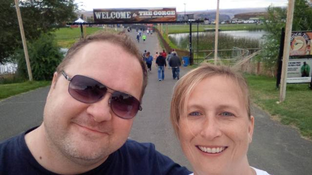 A picture of my husband and I at the entrance to the Gorge in 2014, with the sign above us.