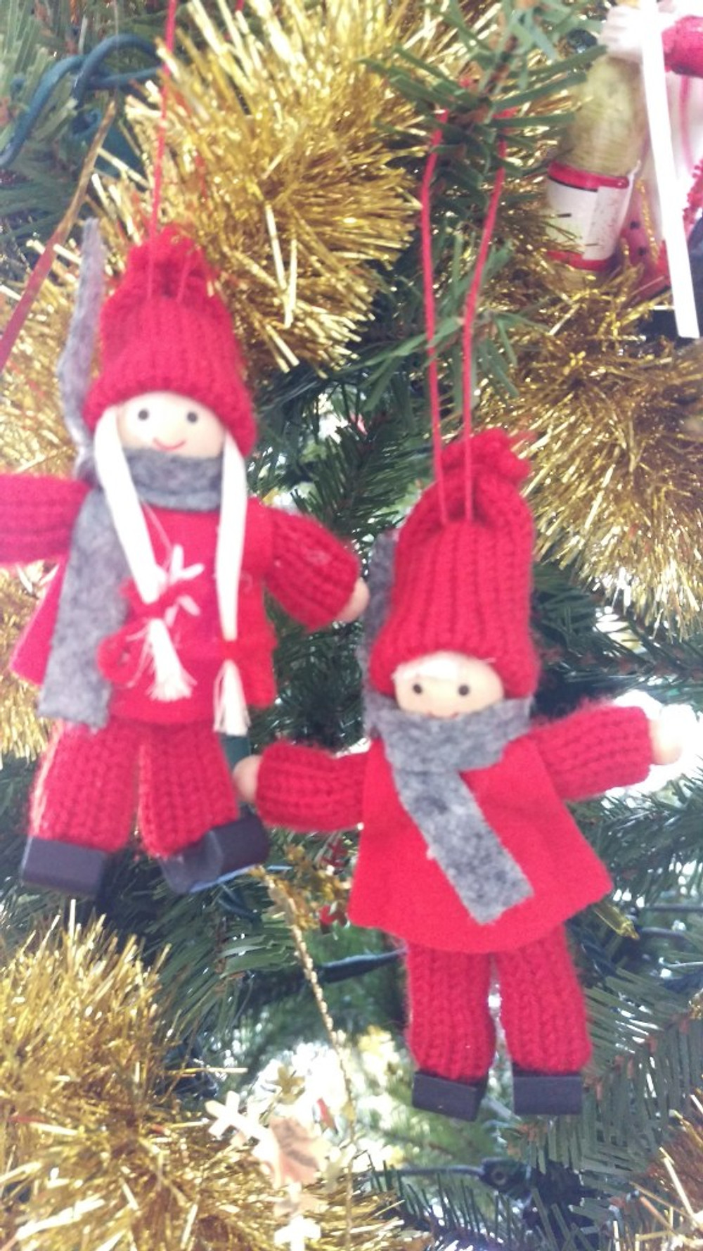 A boy and girl ornament in red yarn snow suits.