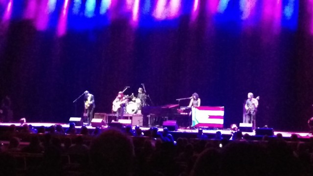 A picture of the band Hurray for the Riff Raff on the stage. There is a Puerto Rican flag on stage as well.
