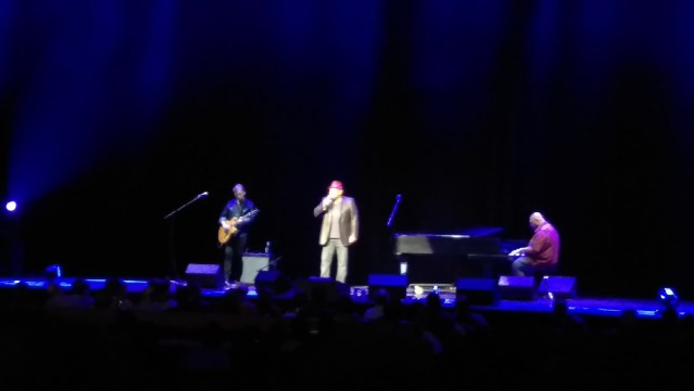 Aaron Neville on stage with his guitar player and pianist on stage with him.