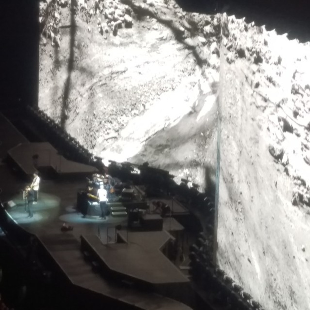 A high up view of U2 on stage with their large video screen in the background.