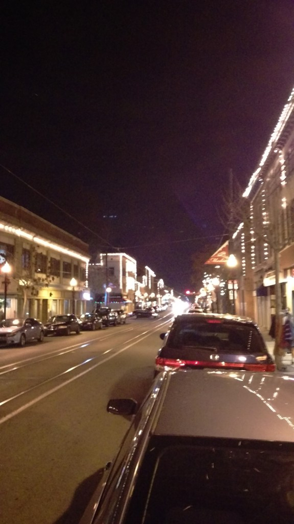A picture of the main street in Media, PA with all of the Christmas lights on the shop fronts.