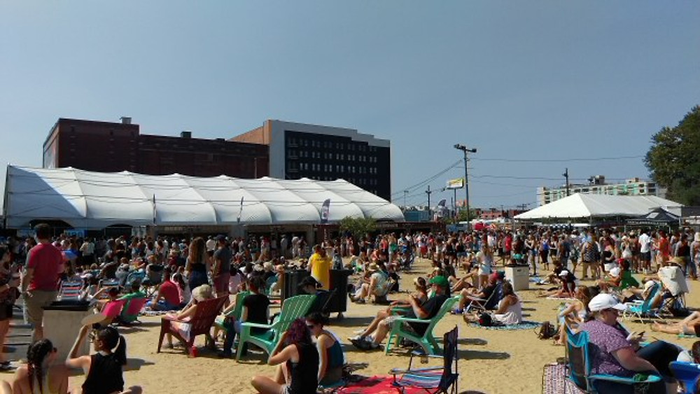A picture of people sitting on chairs and on their blankets, watching a show at Festival Pier.