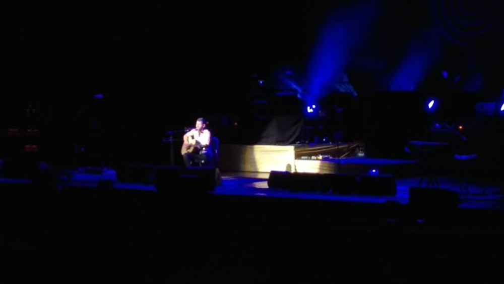 Drew Hagus is sitting on the stage with just his guitar in a small spotlight.